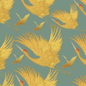 large ornate golden cranes on sage
