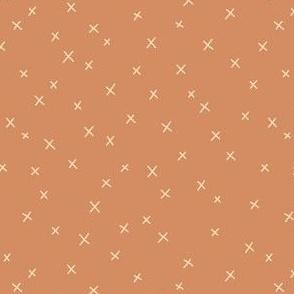 Delicate cross pattern on terracotta brown