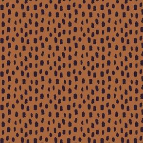 Black marks on brown background