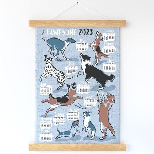 Pawsome 2022 calendar tea towel or wall hanging // pastel blue background // Greyhound Beagle black Border Collie German Shepherd Dalmatian Golden Retriever French Bulldog and Dachshund dog breeds jumping