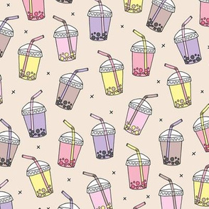Cool celebration bubble tea to go cups with Japanese drinks on soft sand background lilac yellow