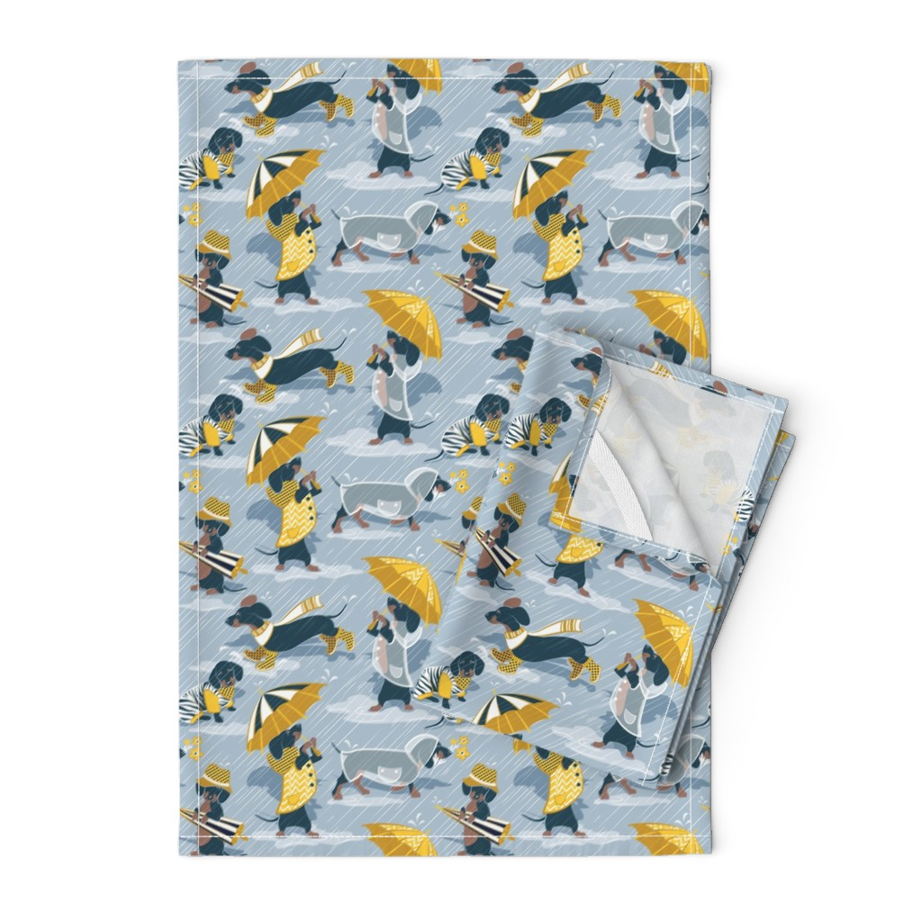 Orpington Tea Towels featuring Small scale // Ready For a Rainy Walk // pastel blue background navy blue dachshunds dogs with yellow and transparent rain coats and umbrellas  by selmacardoso