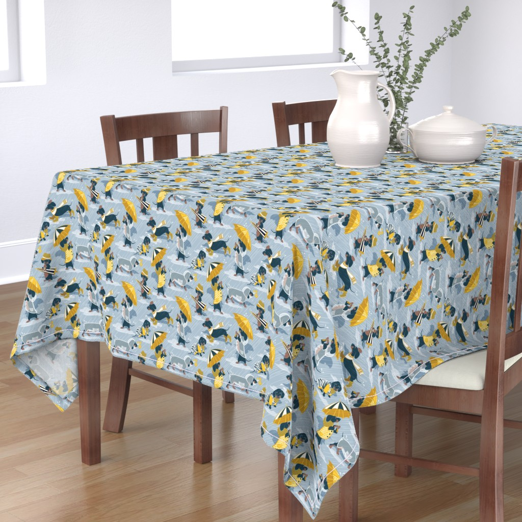 Bantam Rectangular Tablecloth featuring Ready For a Rainy Walk // small scale // pastel blue background navy blue dachshunds dogs with yellow and transparent rain coats and umbrellas  by selmacardoso