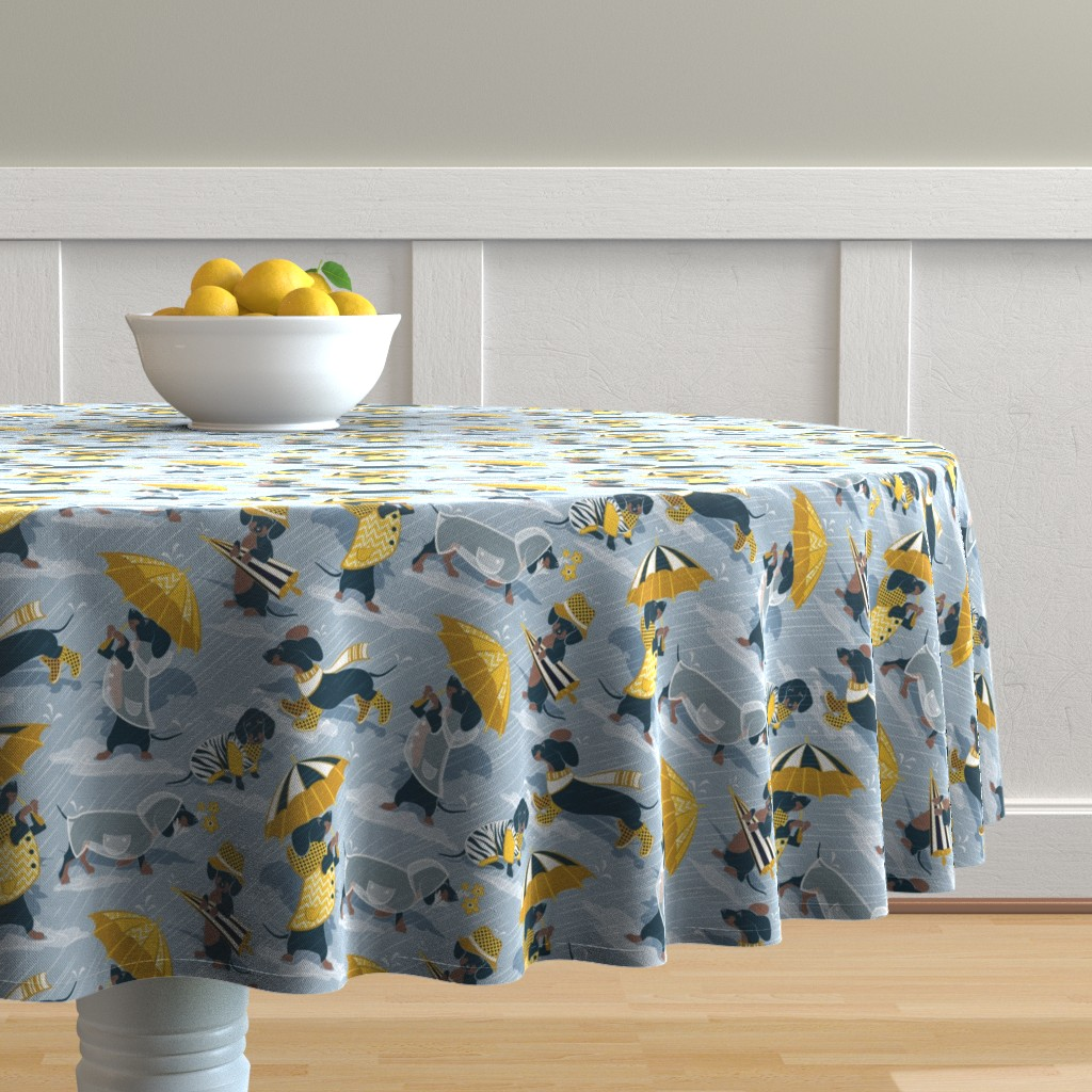 Malay Round Tablecloth featuring Small scale // Ready For a Rainy Walk // pastel blue background navy blue dachshunds dogs with yellow and transparent rain coats and umbrellas  by selmacardoso