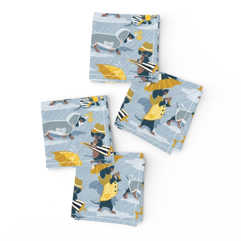 Frizzle Cocktail Napkins featuring Ready For a Rainy Walk // small scale // pastel blue background navy blue dachshunds dogs with yellow and transparent rain coats and umbrellas  by selmacardoso