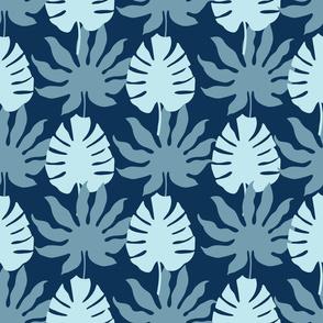 Monstera tropical leaves on dark blue