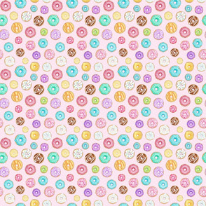 Scattered Rainbow Donuts on pale pink spotty - small scale