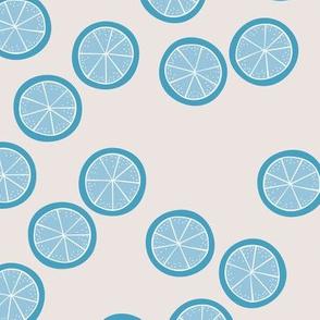 Little slices of lemon bright blue fruit cocktail summer design on beige