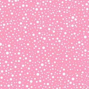 White polka dots on a pink background